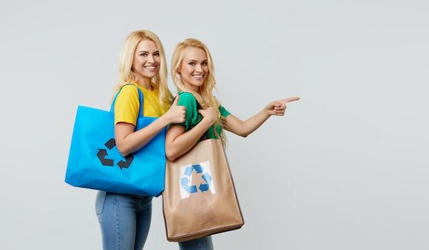 Koncepcja recyklingu. młode kobiety w przypadkowych ubraniach trzymają ekologiczne torby z recyklingu i wskazują prawo do opróżnienia miejsca na tekst.