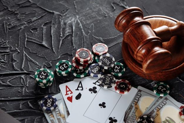 Koncepcja regulacji prawnej hazardu, młotek sprawiedliwości na tle starego szarego stołu.