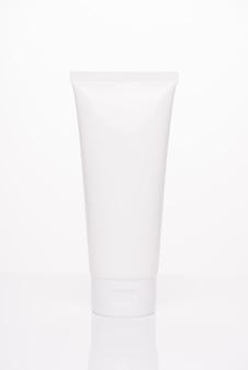 Koncepcja reklamy leczenia makieta ciała. pionowe zdjęcie o pełnej długości plastikowej tuby z pustym miejscem na etykietę kremu do twarzy dla kobiety odizolowanej na białym tle