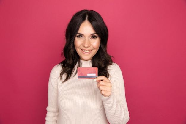 Koncepcja reklamy. pani uśmiechając się i pokazując kartę kredytową na białym tle.