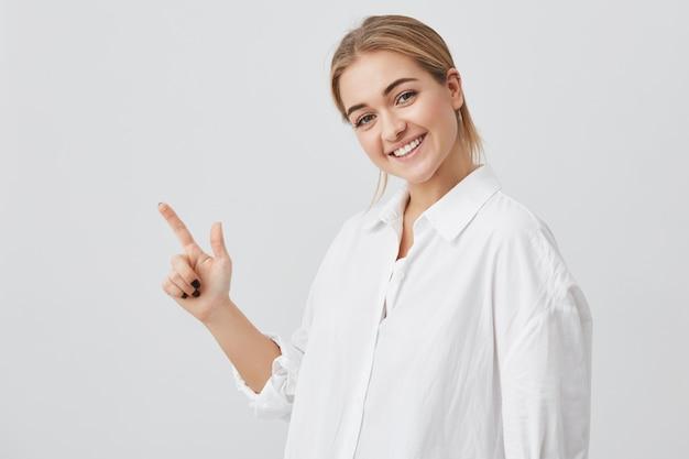 Koncepcja reklamy. szczęśliwa młoda kobieta z blond włosami na sobie ubranie, stojąc z miejsca kopiowania dla informacji lub treści promocyjnych