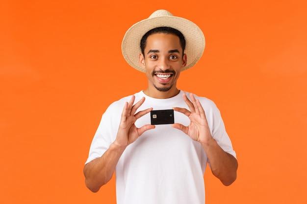Koncepcja reklamy, wakacji i finansów. wszystko czego potrzebujesz to ten bank. rozochocony uśmiechnięty afroamerykański facet w lato kapeluszu, biała koszulka, trzyma kredytową kartę, stoi pomarańczową ścianę