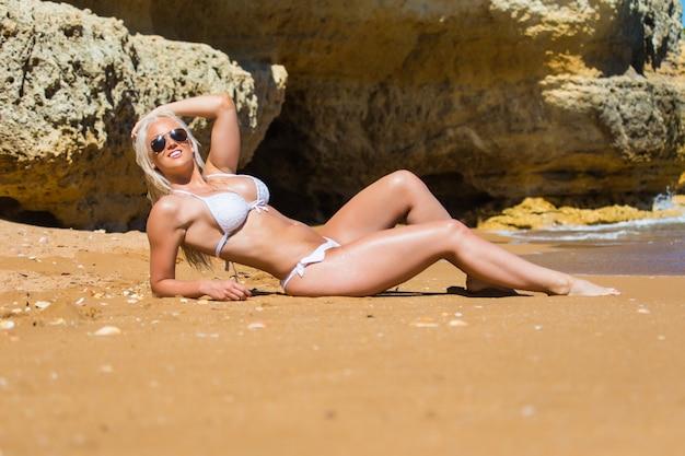 Koncepcja rekreacji i podróży w okresie letnim. piękna opalona młoda modelka w bikini pozowanie na wybrzeżu morza. kobieta w kostiumie kąpielowym kostiumy kąpielowe z mokrymi włosami i ciało na plaży