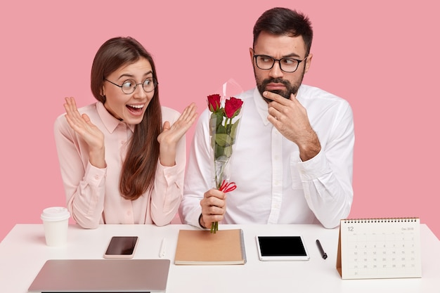 Koncepcja relacji biura. poważny reżyser wręcza sekretarce piękne kwiaty, czuje miłość, umawia się na randkę w miejscu pracy, siada razem przy biurku z elektronicznymi gadżetami. kobieta otrzymuje róże