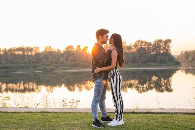 Koncepcja relacji, miłości i natury - atrakcyjna kobieta i przystojny mężczyzna przytulanie i całowanie na ścianie wodnej.