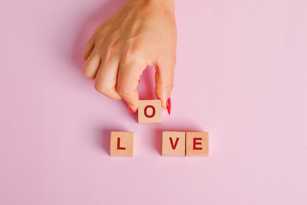Koncepcja relacji płaska leżała. kobieta wyciąga drewnianą kostkę z literami.