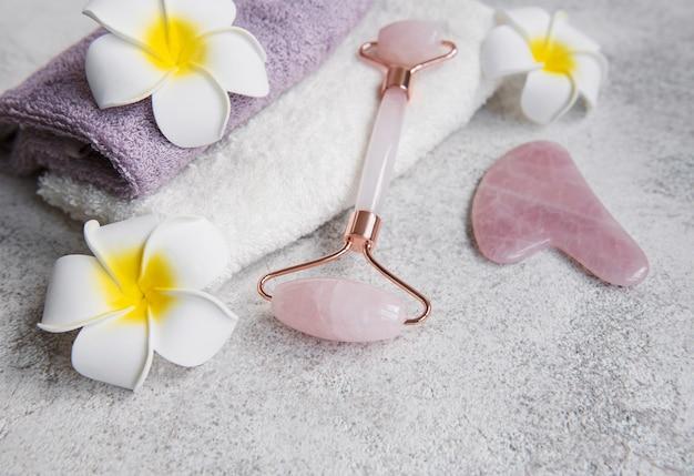 Koncepcja relaks piękne spa. ręcznik, jadeitowy wałek i kwiaty frangipani na szarym tle kamienia.