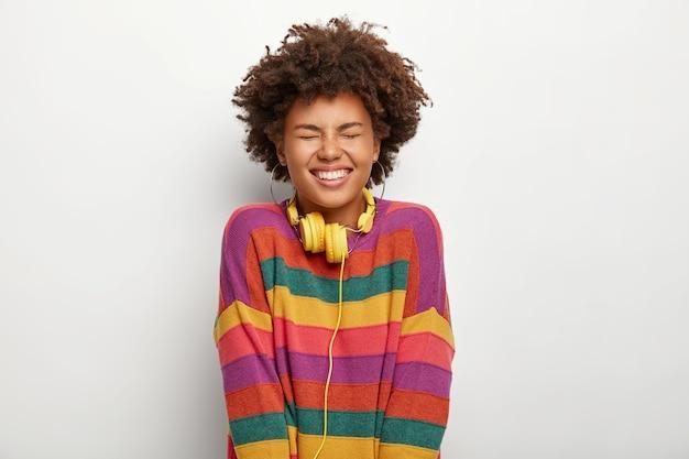 Koncepcja relaksu i dobrego samopoczucia. uszczęśliwiona ciemnoskóra kobieta cieszy się idealnym leniwym weekendem, trzyma oczy zamknięte przed przyjemnością, ubrana w obszerny sweter w paski, używa słuchawek
