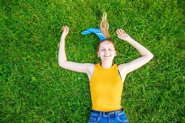 Koncepcja relaksu i medytacji. młoda blondynki dziewczyna kłama na zielonej trawie