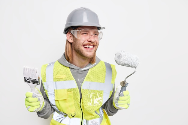 Koncepcja remontu domu. pozytywny rudy brygadzista uśmiecha się radośnie maluje ściany w nowym mieszkaniu trzyma wałek do malowania i pędzel z radością odwraca wzrok