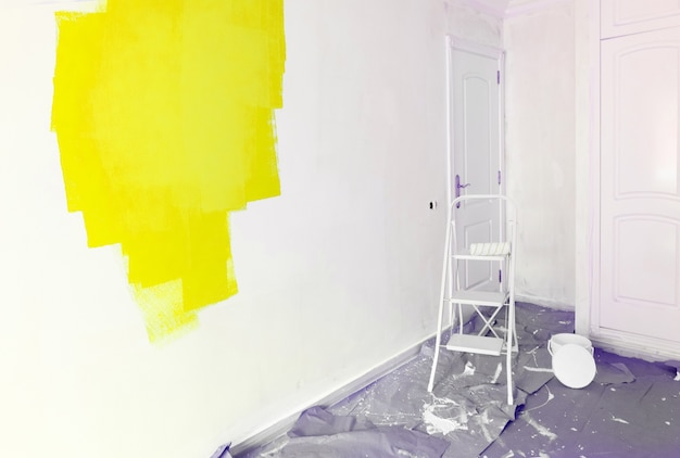 Koncepcja remontu domu - stare mieszkanie w trakcie remontu lub remontu z świecącymi żółtymi plamami farby
