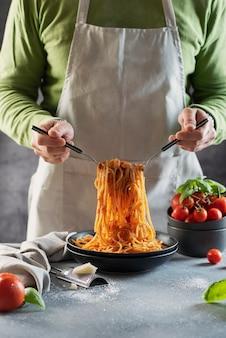 Koncepcja restauracji. mężczyzna gotuje włoskie spaghetti z pomidorami i bazylią, selektywny obraz ostrości