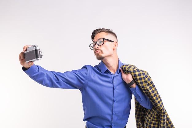 Koncepcja retro aparat, fotografia i ludzie - portret młodego przystojnego mężczyzny robienia selfie na białej powierzchni,