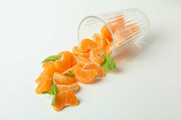 Koncepcja robienia soku mandarynki ze szkła z mandarynek na białym tle.
