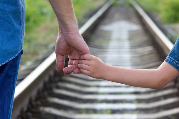 Koncepcja rodzic trzyma za rękę małe dziecko i kolej i kierunek
