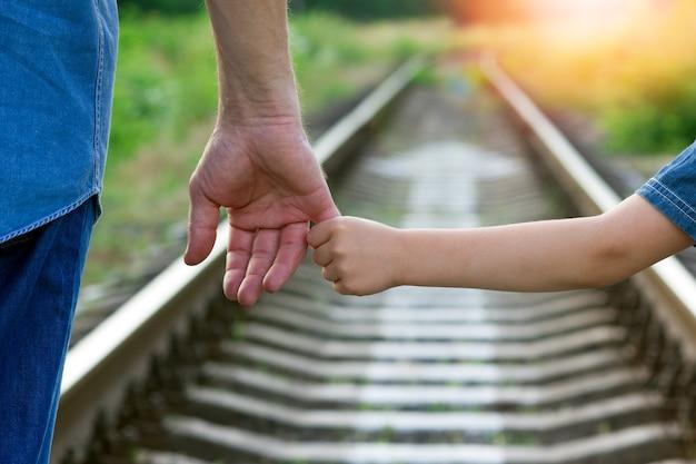 Koncepcja rodzic trzyma za rękę małe dziecko i kolej na przyszłość
