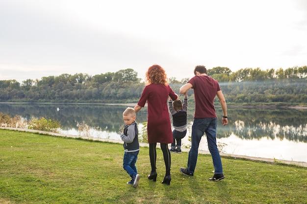 Koncepcja rodzica, dzieciństwa i natury - rodzina bawi się z dwoma synami nad wodą