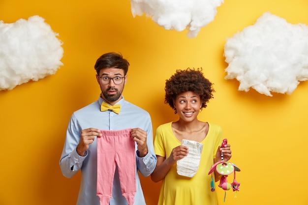 Koncepcja rodzicielstwa, ciąży i noworodka. para przyszłych rodziców czeka na dziecko, kupuje wszystkie potrzebne rzeczy, trzyma ubranka dla dziecka, pieluchę i karuzelę dla nienarodzonej córki lub syna, ma szczęśliwą rodzinę