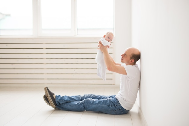 Koncepcja rodzicielstwa, rodziny i ojcostwa. łysy ojciec siedzi na podłodze i trzyma swoje małe dziecko