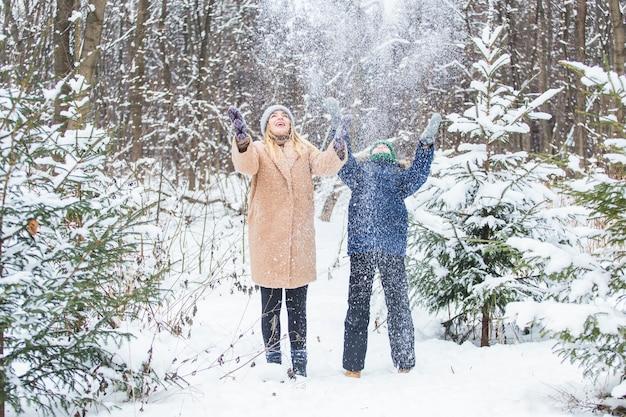 Koncepcja rodzicielstwa, zabawy i sezonu - szczęśliwa matka i syn zabawy i gry ze śniegiem w zimowym lesie.