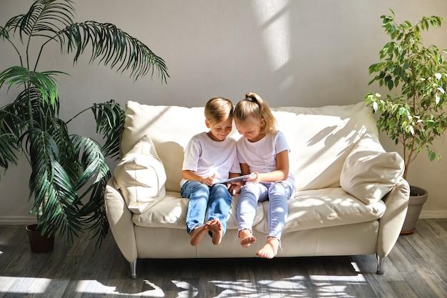 Koncepcja rodziny, dzieci, technologii i domu - uśmiechnięty brat i siostra z komputerem typu tablet pc na kanapie w salonie