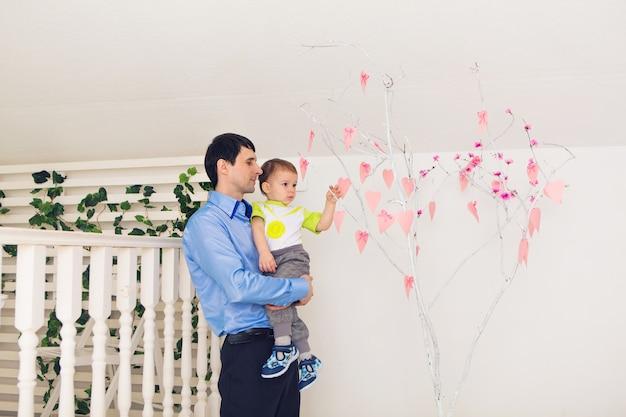 Koncepcja rodziny, dzieciństwa, ojcostwa, aktywności i ludzi - szczęśliwy ojciec i synek bawi się w domu.