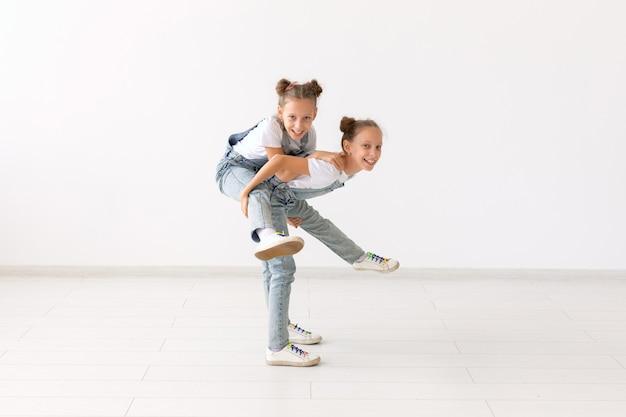 Koncepcja rodziny i miłości - szczęśliwa bliźniacza dziewczyna daje przejażdżkę na barana jej śmiejącej się siostrze.