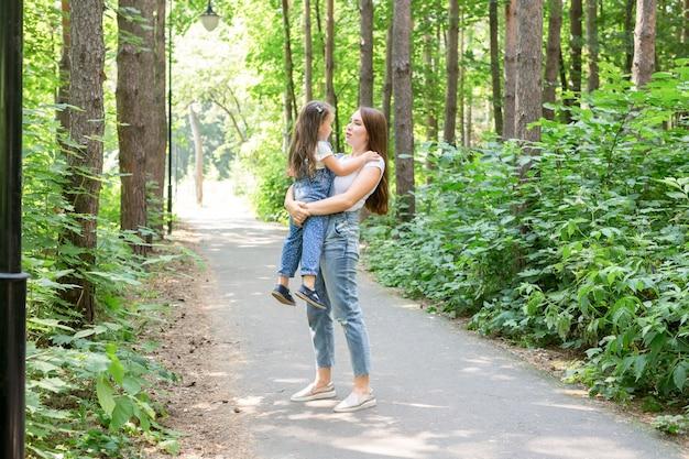 Koncepcja rodziny i przyrody - atrakcyjna młoda kobieta bawić się z córeczką w parku