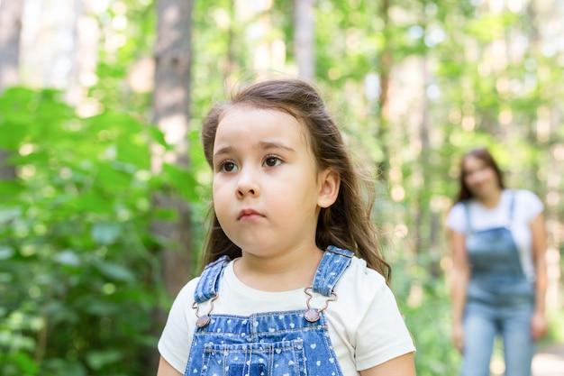 Koncepcja rodziny i przyrody - bliska portret obrażonej dziewczyny dziecka w parku
