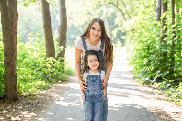 Koncepcja rodziny i przyrody - młoda kobieta przytulić małą dziewczynkę w parku.