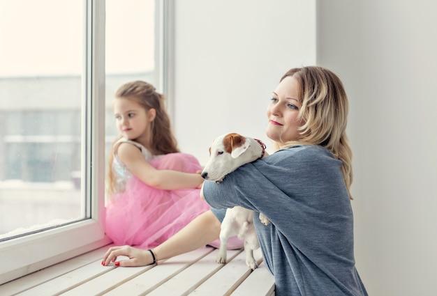Koncepcja rodziny i zwierząt domowych - matka i córka bawi się z psem jack russell terrier w domu.