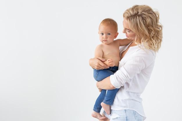 Koncepcja rodziny, macierzyństwa i rodziny - młoda matka trzyma swoje dziecko na białej ścianie