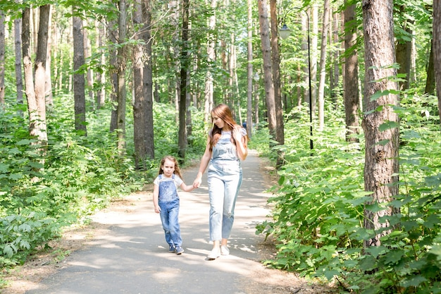 Koncepcja rodziny, przyrody i ludzi - mama i córka spędzają razem czas na spacerze w zielonym parku
