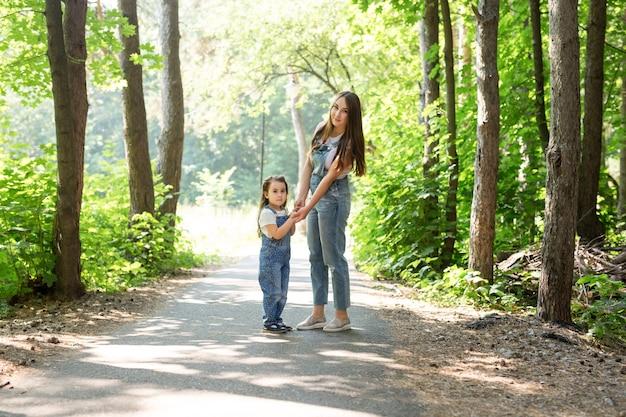 Koncepcja rodziny, przyrody i ludzi - matka i córka spędzają razem czas na spacerze po lesie
