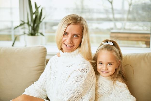 Koncepcja rodziny, relacji, pokolenia, miłości i więzi. stylowa młoda europejska mama z prostymi, długimi włosami, uśmiechnięta, relaksująca się na wygodnej sofie, siedząca obok swojej uroczej córki