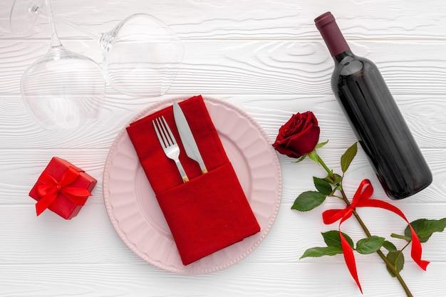 Koncepcja romantycznej kolacji. romantyczne walentynki nakrycie stołu z winem, kieliszkami i czerwonym pudełkiem