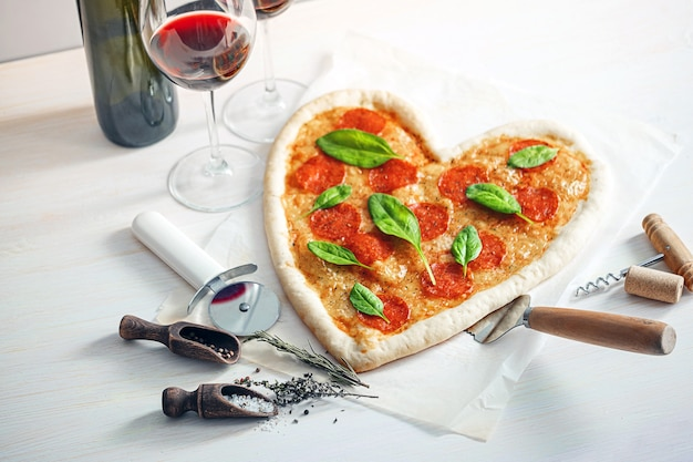 Koncepcja romantycznej kolacji we dwoje z czerwonym winem i pizzą w kształcie serca. kolacja na walentynki