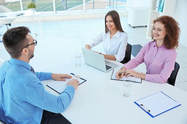 Koncepcja rozmowy kwalifikacyjnej. komisja kadrowa przeprowadzająca wywiad z mężczyzną
