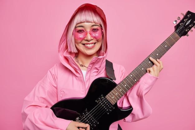 Koncepcja rozrywki i muzyki ludzi. wesoła, modna gitarzystka wers z kapturem gra na gitarze elektrycznej przygotowuje się do koncertu hardrockowego lub festiwalu rockowego