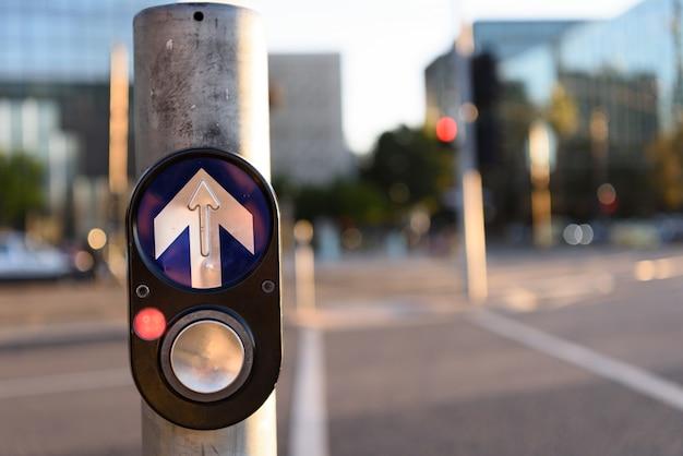 Koncepcja ruchu miejskiego: piesze nacisk, aby przejść przycisk na skrzyżowaniu na rozmytych tła miejskiego.