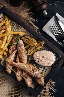 Koncepcja ryby z frytkami, tradycyjne angielskie jedzenie, smażona ryba i frytki. ciemne tło, styl rustykalny