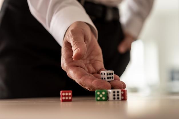 Koncepcja ryzyka biznesowego - biznesmen rzucanie kośćmi na biurku.