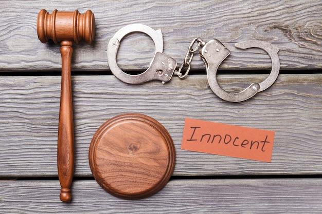 Koncepcja sądu i niewinności. drewniany młotek z kajdankami na biurku.