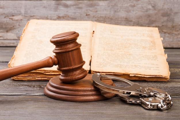 Koncepcja sądu karnego. młotek z kajdankami i starą znoszoną książką z prawami.