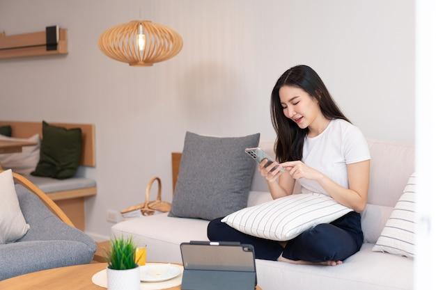Koncepcja salonu długowłosa dziewczyna spędzająca czas na urządzeniach elektronicznych w przytulnym pokoju.