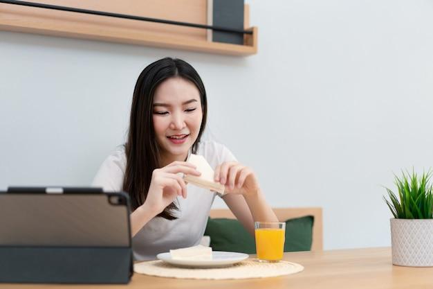 Koncepcja salonu dorosła kobieta korzystających z jedzenia kanapek i soku pomarańczowego oglądania mediów online w przerwie w pracy.