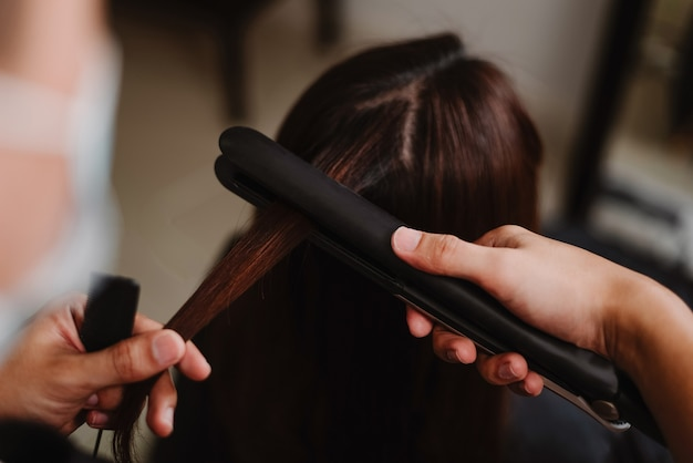Koncepcja salonu fryzjerskiego fryzjer męski pracujący z prostownicą do prostowania włosów klientki.