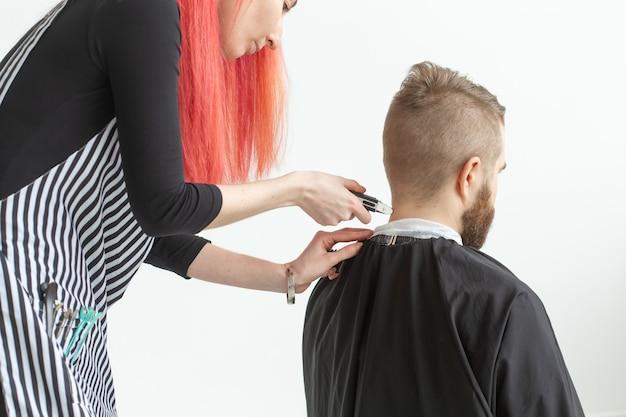 Koncepcja salonu fryzjerskiego, fryzjera i fryzjera - fryzjerka kobieta strzyżąc brodacza.