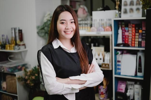 Koncepcja salonu fryzjerskiego ładna fryzjerka pozuje w swoim salonie fryzjerskim w otoczeniu produktów i sprzętu do pielęgnacji włosów