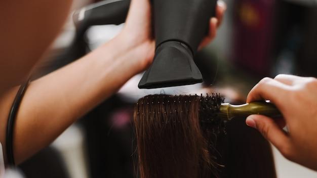 Koncepcja salonu fryzjerskiego męski fryzjer używający grzebienia do chwytania kosmyka włosów i używania suszarki do suszenia i prostowania